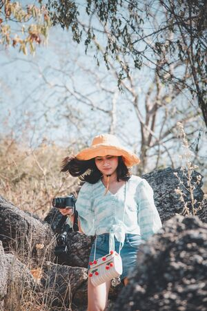 Asian pretty cute woman short jeans with hat hiking in forest on mountain with cliff with happy and freedom emotion in concept travel, active lifestyle, vacation, overcome obstacles in life