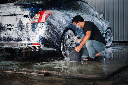 Car care staff cleaning (clean, wash, polish, wax and glass coating) the car (Car detailing) at car care shop in Bangkok Thailand