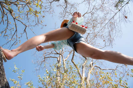 Low angle view of woman short jeans midair by jumping, crossing step over camera shot below in forest with tree and sky overhead in concept travel, active lifestyle, overcome obstacles in life Standard-Bild