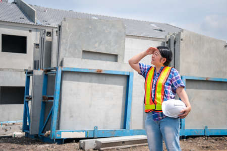 Asian woman civil construction engineer worker or architect with helmet and safety vest happy working at a building or construction site