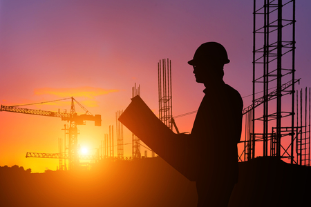 Ingénieur de silhouette à la recherche de travailleur de la construction dans un chantier au coucher du soleil Banque d'images