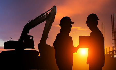 Silhouette Businessman engineer looking blueprint in a building site over Blurred construction site film grain progress and potential concepts. Banco de Imagens