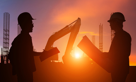 Silhouette Teams engineer looking construction worker in a building site at sunset Banco de Imagens