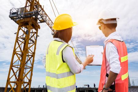 Equipo de ingenieros que buscan planos en un sitio de construcción sobre progreso de grano de película de sitio de construcción borrosa y posibles conceptos.