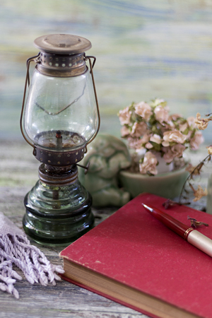 oil lamp: Old oil lamp, book and ceramic on wooden table.