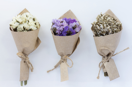 Line of Three sundried flower bouquets wrapped in light brown kraft papeer with tag isolated on white bacgound. Presened in mood in love concept.