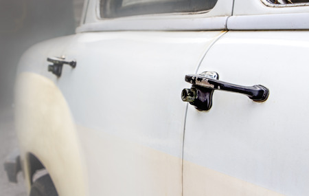 The old abandoned vintage car in the garage, door handle of the old car. Stock Photo