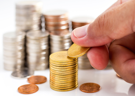 Coins stack and hand picked golden coin on the white table. the concept of business growth, financial or money savings Stock Photo