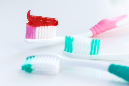 Red toothpaste is on the toothbrush on white background. Dental Care Concept. with copy space for text.  Stock Photo