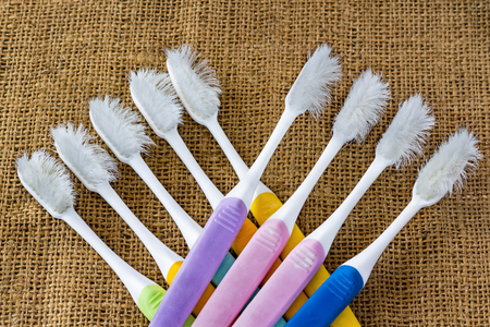 Several toothbrushes dilapidated placed on a brown sackcloth. Dental Care Concept. Stock Photo