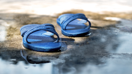 A pair of rubber old sandals on the concrete floor.