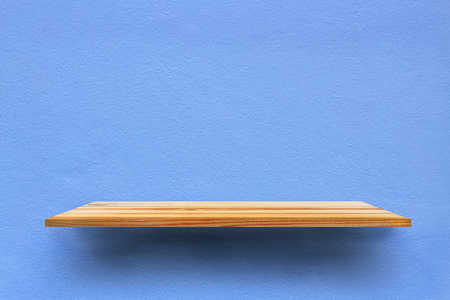 Wooden shelf on the blue stone wall for background design.