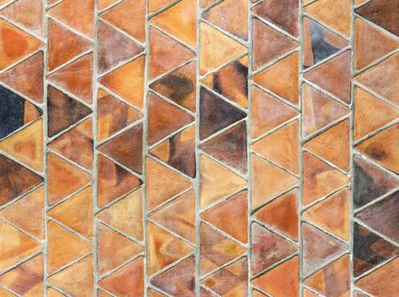 a triangle slab of baked clay, used in overlapping rows for covering the wall.  banked clay wall texture for background.