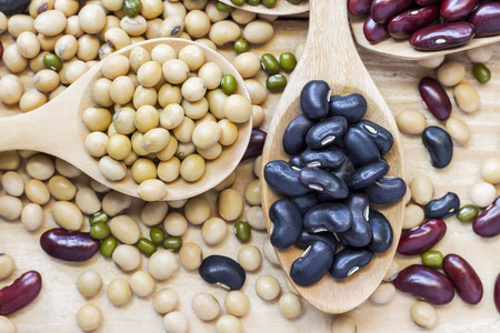 Many types of beans are separated in a spoon on a wood table such as mung bean, soybean, black bean, red bean. Stock Photo