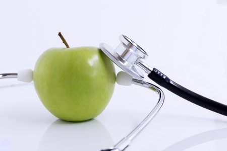 Stethoscope and green apple isolated on white table background. The stethoscope is a medical instrument for listening to the action of someone's heart or breathing. with copy space for your text.