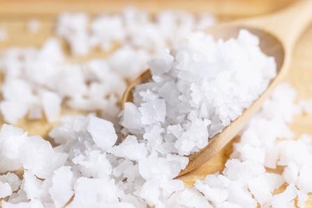 Seesalz in einem hölzernen Löffel auf dem Tisch. Meersalz wird zum Würzen, Konservieren von Lebensmitteln und zur Schönheitsbehandlung des Peelings mit Salz verwendet. selektiver Fokus.