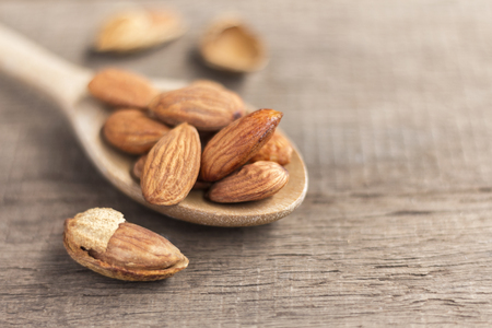 Almonds in the wooden spoon on the table. Almonds are rich in nutrients, vitamins and minerals that are essential to the body.
