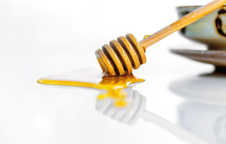 Golden sweet honey with a wooden honey dipper on the white ceramic background. Honey is a sweet, sticky, golden fluid made by bees.