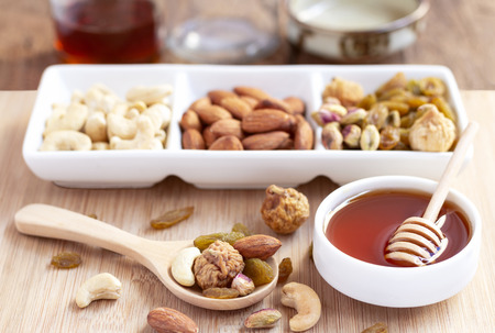 Dried fruits and variety of nuts into a dish and bowl of honey on the wooden background, such as figs, almonds, raisins, cashews, and pistachio.