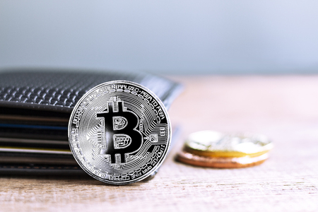 Bitcoins and leather wallet on the wooden table. Virtual money or cryptocurrency concept. with copy space for your text.