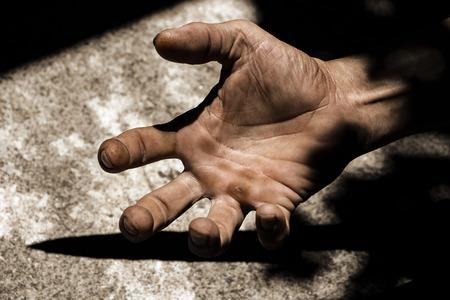 Las manos de los hombres en la oscuridad con la luz tocando la piel, el concepto de frustración y estrés.