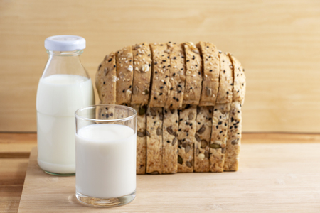 A glass of milk and bread placed on the wood table. with copy space for text. Imagens