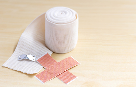 Elastic adhesive bandage and adhesive plaster as first aid to treat those injured. Copy space for your text.