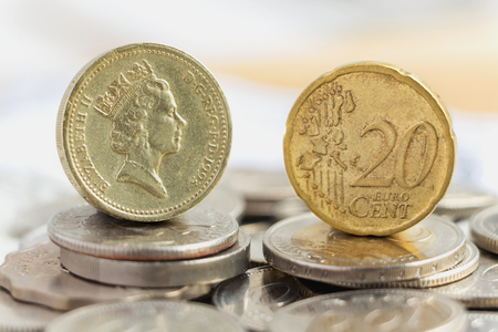 Euro coin and British one pound coin on a pile of coins. The concept of the main currency exchange can be used worldwide. Stock Photo