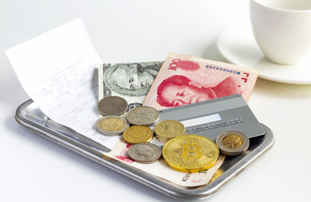 Bitcoin, coins, and banknote placed on stainless steel small rectangle tray with a cup of coffee on the wooden table. The concept of virtual money or cryptocurrency that is used in daily life.