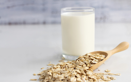 A glass of milk and oats in spoon on the white table. Its are a nutrient-rich food associated with protein and fiber.