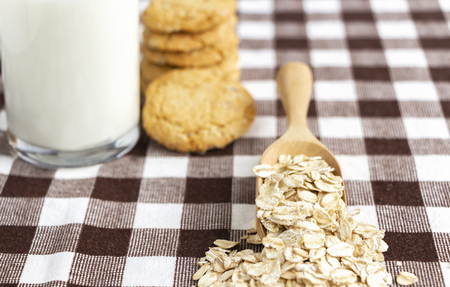 Dried oat in spoon and oatmeal cookies on the white table. Its are a nutrient-rich food associated with protein and fiber. 免版税图像