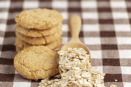 A pile of cookies and oats in spoon on the wooden table. Its are a nutrient-rich food associated with protein and fiber.