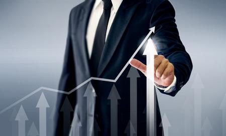 A successful businessman, hands touch the graph that represents profit rises on a lot more. Reklamní fotografie
