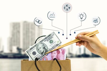 The hand of female holds the chopsticks, which clamp yuan and the dollar banknote out of the paper bag.The concept of business growth, financial or trade economy. Stock Photo