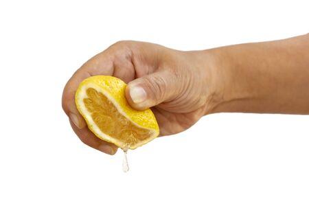 Main de femme pressant une moitié de jaune citron frais sur fond blanc.
