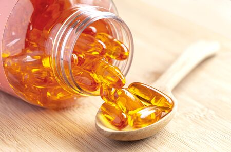 Fish oil capsules as a dietary supplement containing omega-3 and vitamin a is high for health care. Salmon oil into spoon on the wood table. Stock Photo