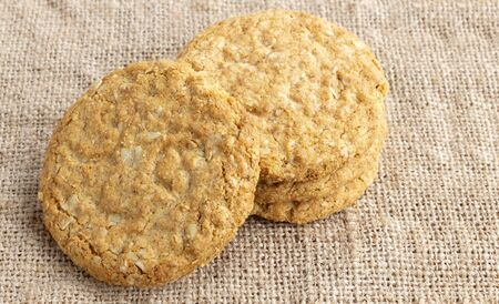 Homemade oat and wholemeal biscuits isolated on brown sackcloth background. Its are a nutrient-rich food associated with protein, fiber and no artificial flavours or colour added.
