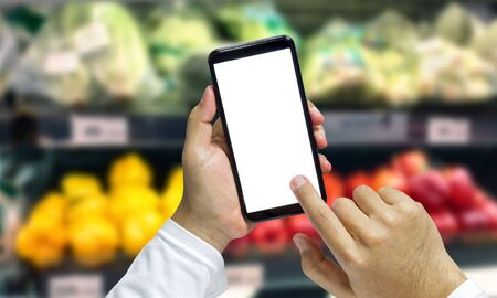 Shopper Mobile smart phone in hand, and see more detail and compare the prices in supermarkets.