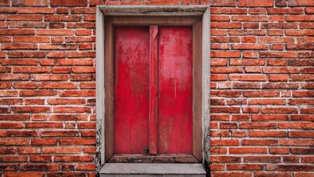 Large red wooden door and red brick wall texture background. The old vintage retro door made of hardwood.