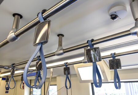 A Hand hold strap inside rapid transit train.Plastic Handle Grabs Train Hand Hold. 免版税图像