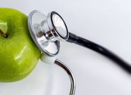 Stethoscope and green apple on white table background. Fresh fruit is good for health.
