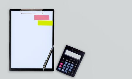 Black clipboard, pen and calculator on grey color background.