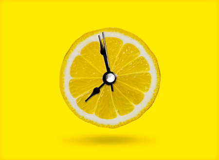 Lemon and the clock are the idea of ​​a healthy breakfast or a bright morning awakening.