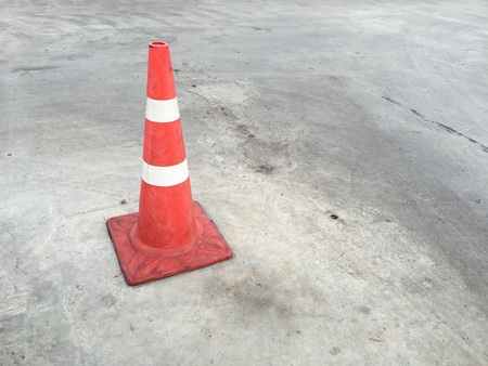 vertical divider: Red and white striped warning cone on road.