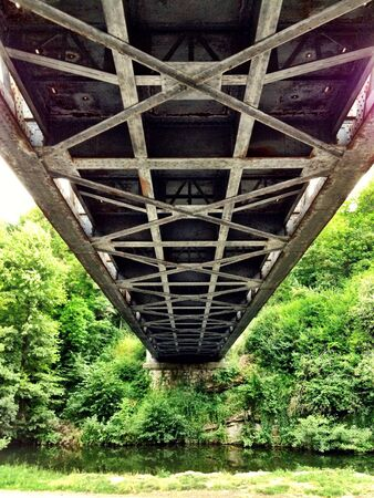 Under a metal bridge leading to green space