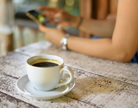 Black coffee with women using the phone behind. Stock Photo