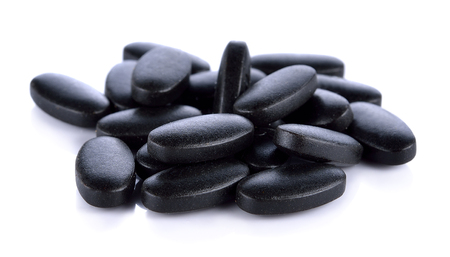 vitamins mix charcoal pills on white background Stock Photo