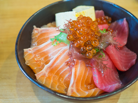donburi, japanese food made by fresh salmon, tuna, seaweed and rice (focus salmon)