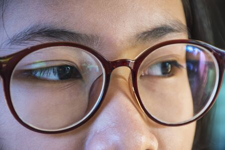 Close-up of glasses worn by an Asian girl With a black background. The subject has beautiful reflections on the glasses.