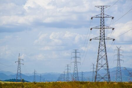 high voltage post.High-voltage tower Located on a brown field.which has mountain and sky background. Stock Photo